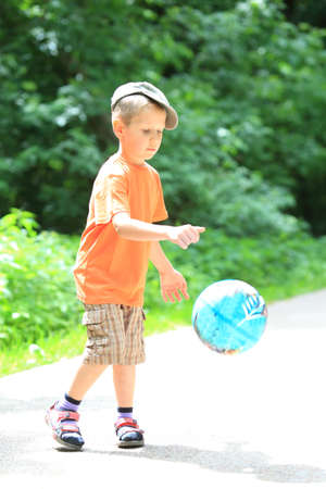 Boy in action young kid playing with ball in park outdoors. Healthy leisure time photo