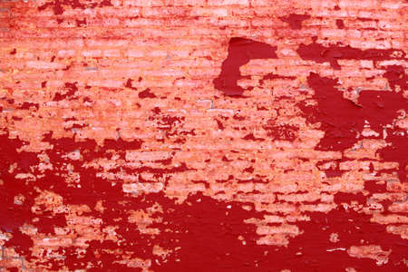 Old weathered painted red brick wall fragment grunge background photo