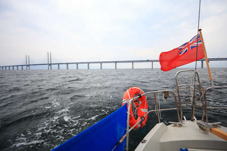 Oresundsbron. The Oresund bridge link between Denmark and Sweden, Europe, Baltic Sea. View from sailboat under UK british ensign. Overcast stormy sky. photo