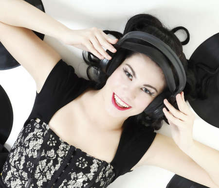 Sexy happy girl with headphones, retro style studio shot photo