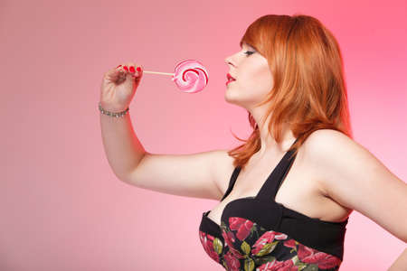 happy young redhair woman with lollipop candy pink background photo
