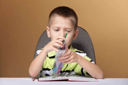 little boy kid drawing with color pencils photo