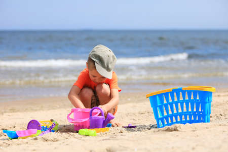 little boy playing with toys on beach photo