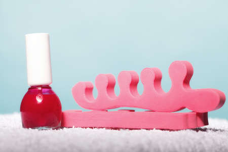 separators: Pedicure accessories of red nail polish bottle and pink toe separators on blue background