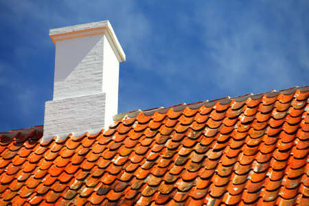 undulate: The old roofing tiles red clay house roof with chimney sky background