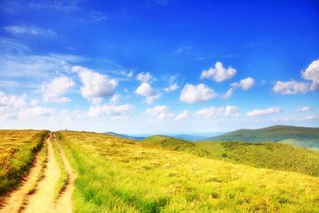Beautiful summer landscape in the mountains. Pathway through the grassy hills, blue sky with clouds Bieszczady Poland photo