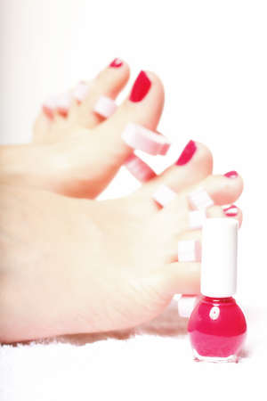 separators: foot pedicure applying womans feet with red toenails in toe separators white background
