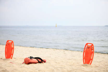 Lifeguard rescue equipment orange preserver tool, red plastic buoyancy aid in the sand photo