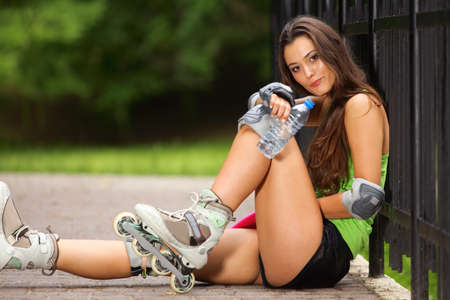 Happy young girl enjoying roller skating rollerblading on inline skates sport in park photo