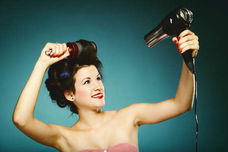 funny girl styling hair with curlers hairbrush and hairdryer retro style blue background photo