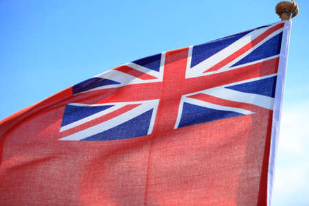 ensign:  The UK red ensign the british maritime flag flown from a yacht sail boat blue sky