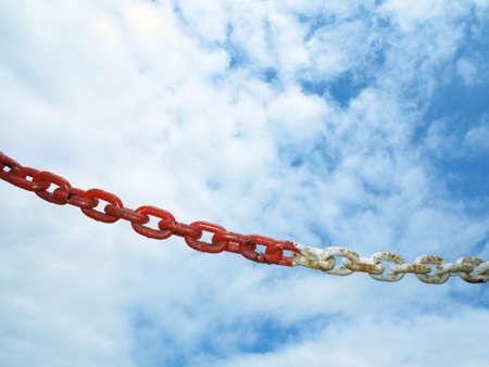 interlinked: Old metal oxidado de acero rojo segmento de las conexiones de cadena. Cielo nublado de fondo. Foto de archivo
