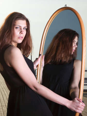 thoughtful young woman looks at the reflection in the mirror - solitude lonely concept Stock Photo - 22039501