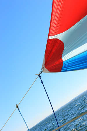 spinnaker: The wind has filled the spinnaker on sailing yacht. Detail of a colorful sail against the deep blue sky. Stock Photo