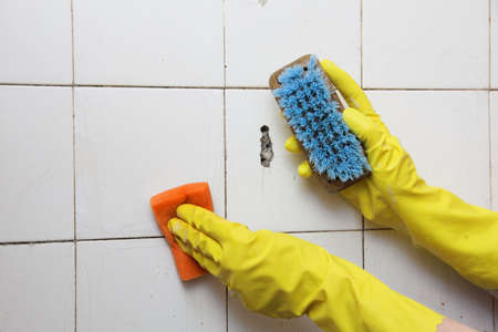 Gloved Hand Cleaning Dirty Old Tiles With Brush In A Bathroom Stock