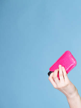 Female hand holding mobile phone in pink cover blue background with copy space photo
