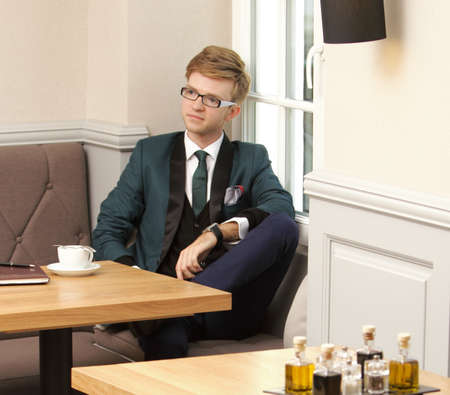 Young handsome stylish man fashion model relaxing thinking and waiting in cafe restaurant with coffee photo
