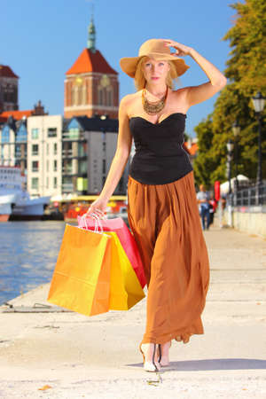 Stylish autumn shopper woman in hat with shopping sale bags in european city, old town Gdansk in the background, Poland Europe photo