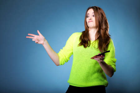 Happy girl with mobile phone pointing her finger make silly faces, doing grimace, blue background photo