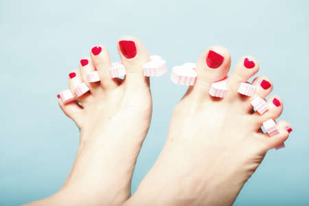 foot pedicure applying womans feet with red toenails in pink toe separators blue background photo