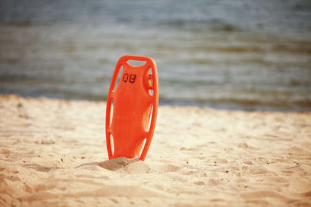 Beach life-saving. Lifeguard rescue equipment orange preserver tool, red plastic buoyancy aid in the sand Stock Photo - 22175330