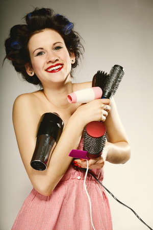 young woman preparing to party having fun, funny girl with curlers and many accessories for styling hair comb brushes hairdreyer retro style grey background photo