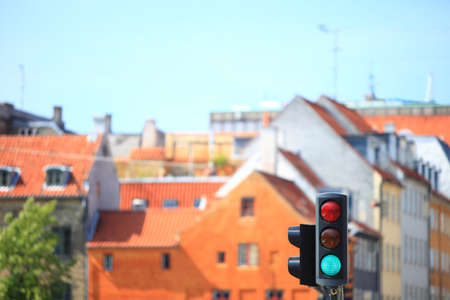 Green color on the traffic lights against city background photo