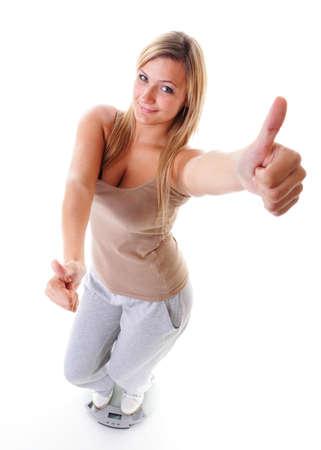 Femme de taille plus grande fille heureuse avec une �chelle de poids c�l�brer les progr�s perte de poids apr�s r�gime, le pouce jusqu'� geste, elle a perdu un peu de poids. Concept des modes de vie sains