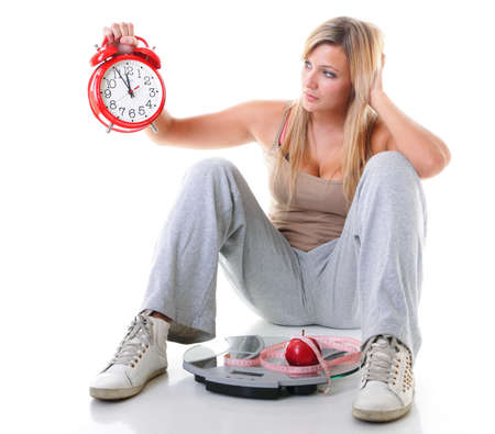 oversize: Time for diet slimming. Woman plus size large girl with clock scales apple measuring tape - weight loss concept. Isolated on a white background.