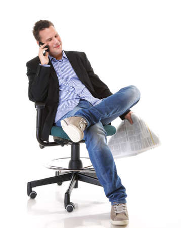 commenting: Full length businessman reads newspaper phoning talking on mobile phone commenting economy news isolated on white background