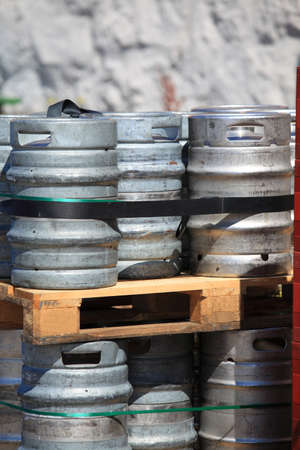 Lots of metal barrels beer kegs on the wooden palettes at factory brewery photo