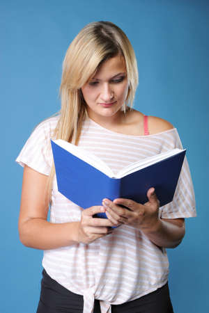 Student girl with open book, young woman reading on blue\ background