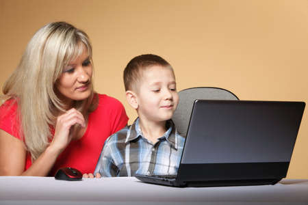 mother with son together looking on the laptop orange background photo
