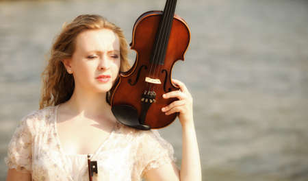 Portrait of blonde girl music lover on beach with a violin. Love of music concept. photo