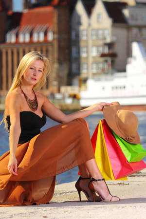 Stylish autumn shopper blonde woman with shopping sale bags in european city, old town Gdansk in the background, Poland Europe photo