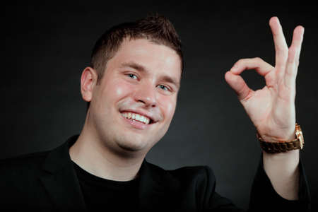 Happy Satisfied man gesturing the all right symbol, showihg ok sign black background photo