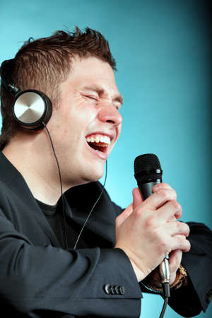 signer: Young man singing into microphone. Happy karaoke signer studio shot blue background Stock Photo