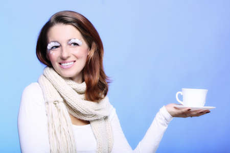 Fashion woman stylish winter makeup holding cup of hot drink beverge enjoying coffee time copyspace blue background photo