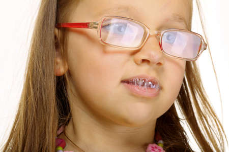 drool: Funny little girl in glasses doing fun saliva bubbles studio shot isolated on white background Stock Photo