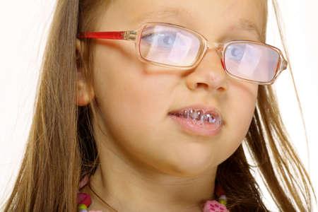 spitting: Funny little girl in glasses doing fun saliva bubbles studio shot isolated on white background Stock Photo