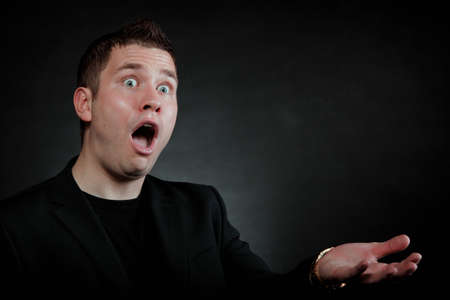 surprised shocked man face hand gesture wide eyed black background photo