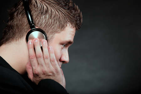Profile of a man student with headphones listening to music black grunge background photo