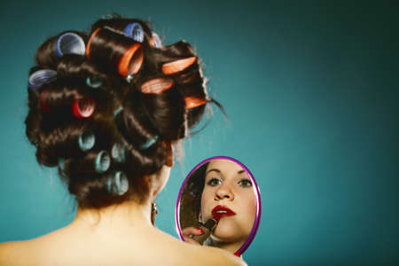 young woman preparing to party, girl styling hair with curlers applying make red lipstick in hand looking at mirror up retro style blue background photo