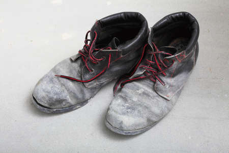 pair of old dirty work boots in construction site photo