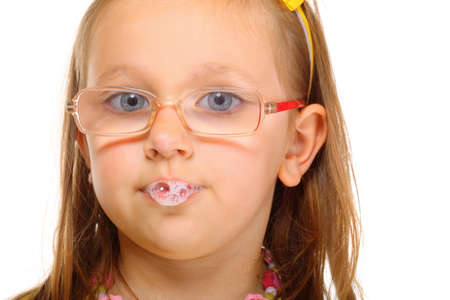 Funny little girl in glasses doing fun saliva bubbles studio shot isolated on white background