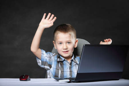 triumphing: Triumphing child boy with a laptop notebook computer on black background. Computer addiction. Stock Photo