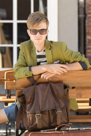 waits: Young handsome man traveler casual style sitting on bench with bag waits, old town Gdansk Poland Europe Stock Photo