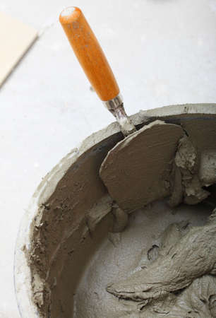 Renovation at home dirty trowel and bucket with mortar on construction building site Stock Photo - 22362634
