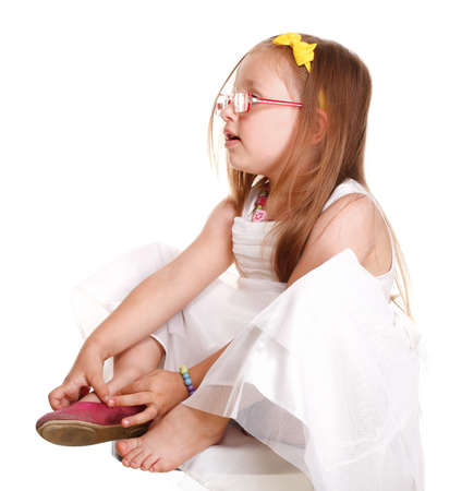 child little girl tries to put on her shoes isolated on white background photo