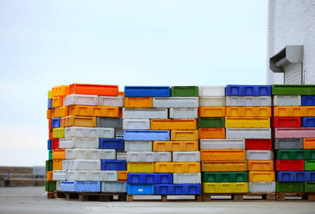 colorful boxes plastic crates. Packing containers piles for fish storage of catch. photo
